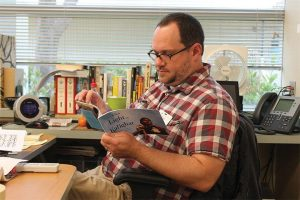 PUBLISHED PRO Teacher Kyle Vaughn peruses his recently published book. Photo by Sydney