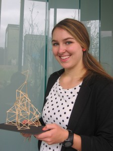 WORK OF ART Sophomore Katherine proudly displays her toothpick sculpture  at the exhibition. Photo by Noor