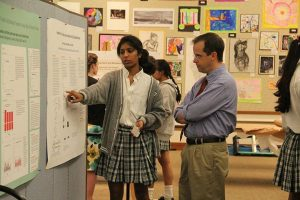 SUMMERTIME SCIENCE Junior Aashima Garg shows her  summer science research to Science Department Chair Dr. Marshall Bartlett at a science research symposium on Sept.19. PHOTO BY SYDNEY YONACK