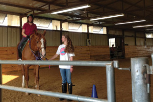 TAKING THE REINS Sophomore Raney Sachs leads a rider in the indoor arena at Equest. Photo taken by Carol Battalora