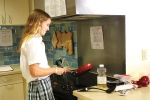 MASTER CHEF  Junior Elizabeth Michel demonstrates her cooking skills in the Tarry House kitchen. PHOTO BY AUDREY KIM