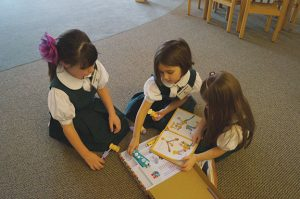 BUILDING TOGETHER Pre-K students Jameson Dondero, Gwendolyn Becker and Maggie Hurley play with a Goldieblox construction set, a toy designed to encourage girls to build their engineering skills. PHOTO BY ALAINA RODRIGUEZ