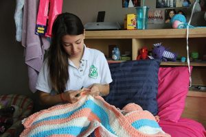 "BABY BLANKET Senior Shelby Cohron crochets a blanket for College Counseling Associate Courtney Skerritt, who is expecting a baby girl in August. She began crocheting the blanket before she found out the baby's gender. ""It's gender neutral,"" she said. PHOTO BY TIFFANY LE"