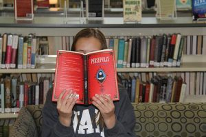 """BEHIND THE COVER Freshman Camryn Dixon reads Satrapi's """"Persepolis,"""" a novel that is often banned at other schools but is part of the freshmen English curriculum at Hockaday. Credit: Mary Orsak/The Hockaday Fourcast"""