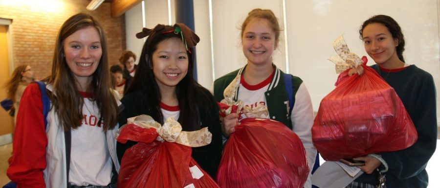 Seniors Kate Keough, Jenny Zhu, Melanie Kerber and Nicole Klein find the red bags filled with gifts from the Angel Tree. // Photo by Sonya Xu