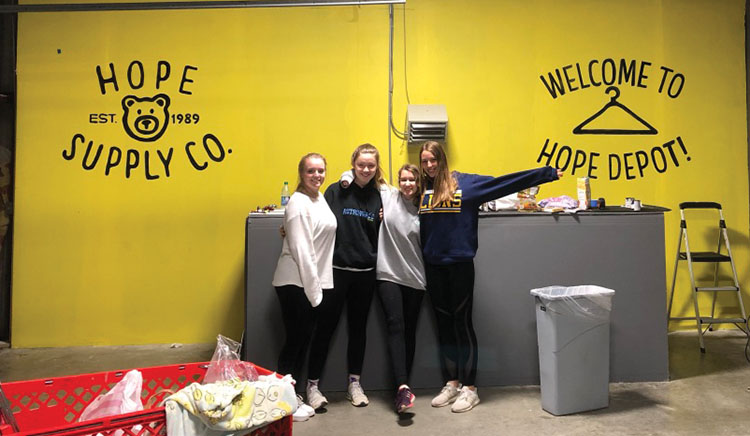 Seniors Nancy Dedman, Zoe Cote, Kemper Lowry, and Elena Dewar show off the mural they created to brighten up the Hope Supply warehouse. photo courtesy of Elena Dewar