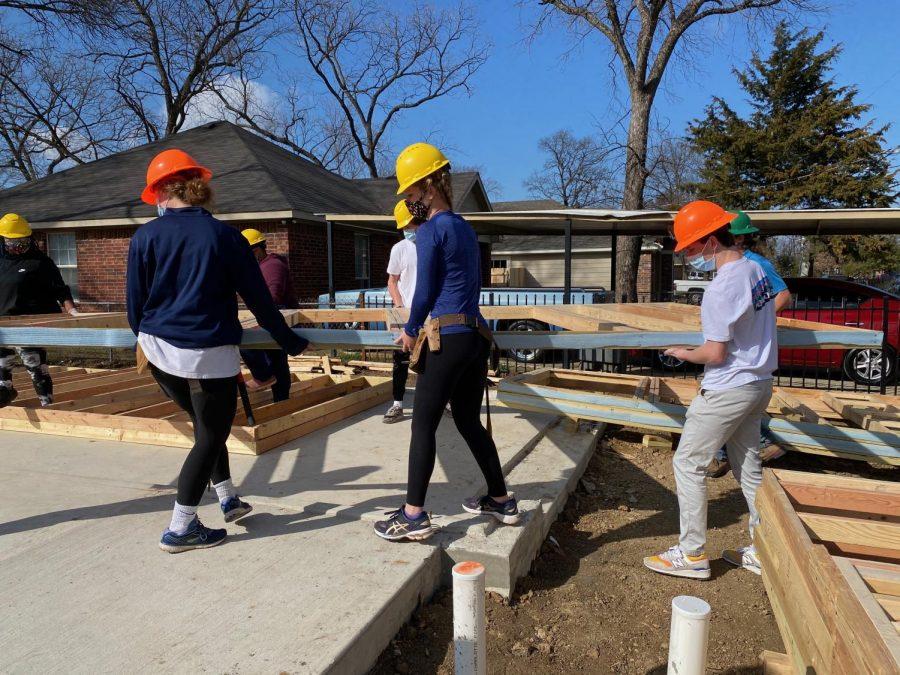 Habitat+volunteers+move+equipment+and+materials+at+a+build+site.%0A