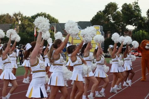 Cheerleaders hype up the crowd before a play at the first home game of the year.